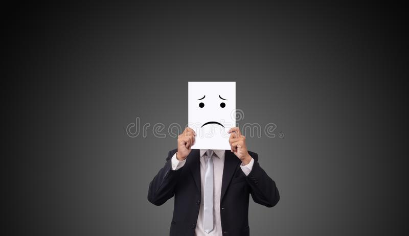 Businessman wearing suit with drawing facial expressions emotions feelings on white paper.  stock photo
