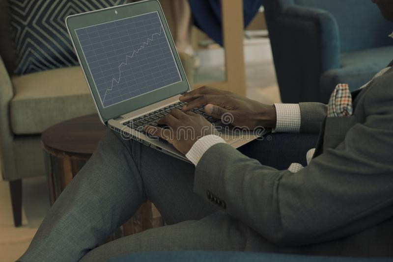 Businessman wearing suit holding laptop on his lap and looking into banking charts royalty free stock photos