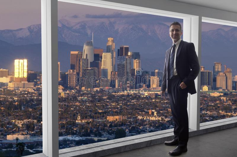 Businessman in an office looking at the view of downtown Los Angeles royalty free stock image