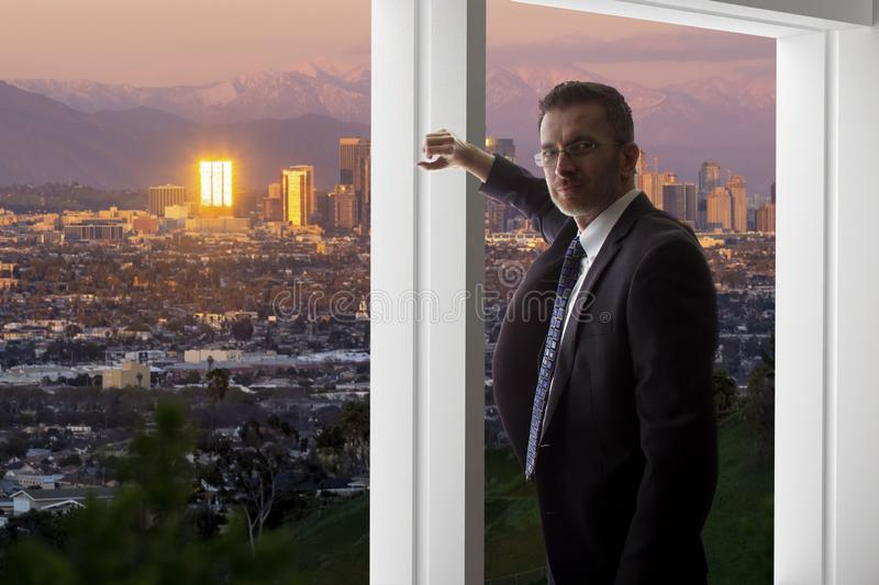 Businessman in an office looking at the view of downtown Los Angeles royalty free stock photos