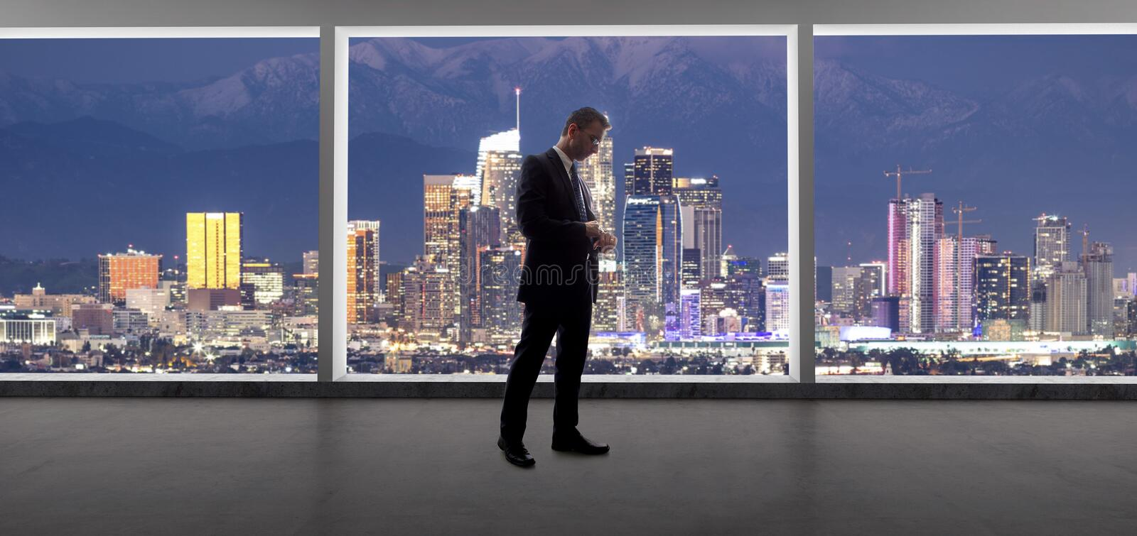 Businessman in an office looking at the view of downtown Los Angeles royalty free stock photo