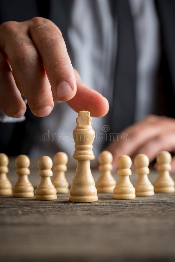 Businessman wearing suit moving the king piece in a close up vie stock photography
