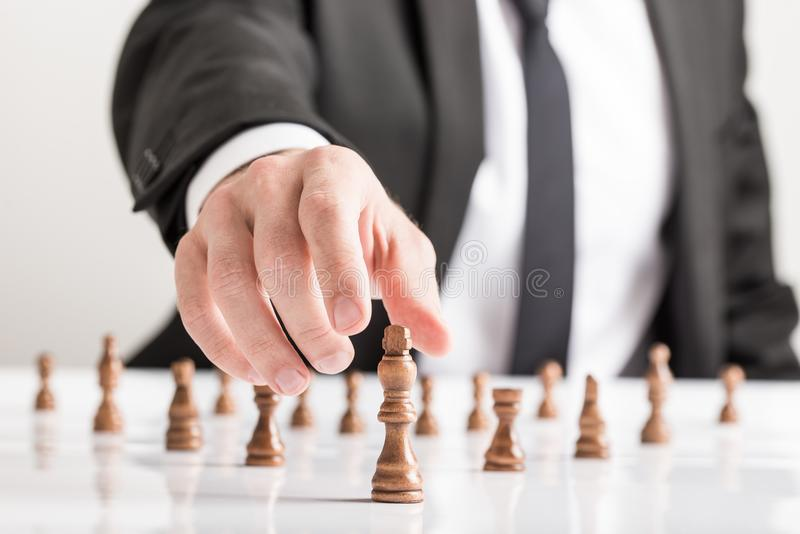 Businessman wearing suit playing chess reaching dark king piece. On white table. Conceptual of business vision royalty free stock photography