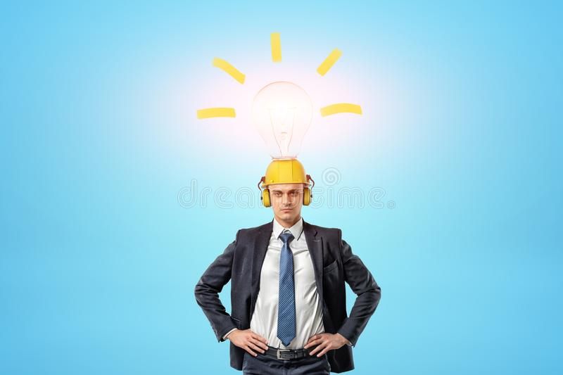 Businessman wearing yellow safety helmet with light bulb above on blue background. Industrial technology. Business ideas. Safety equipment royalty free stock photography