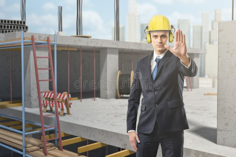Businessman wearing yellow safety helmet and showing stop gesture at construction site royalty free stock photo