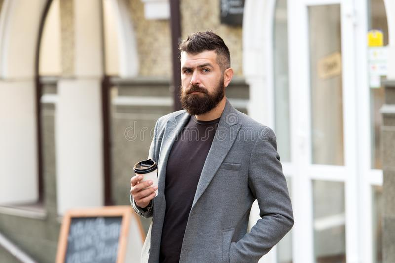 Businessman well groomed appearance enjoy coffee break out of business center. Relax and recharge. Man bearded hipster royalty free stock photo
