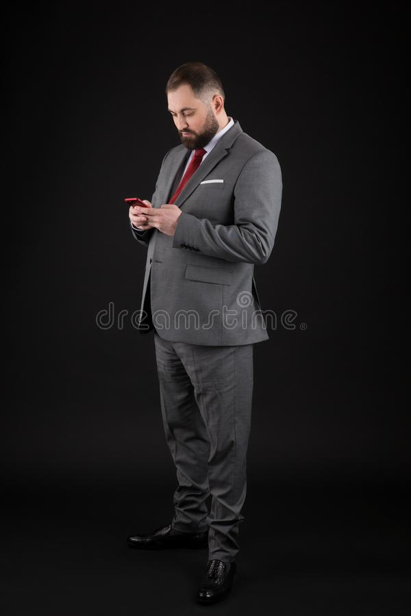 Businessman well groomed man hold smartphone. Man formal suit use smartphone social networks. Guy surfing internet smartphone stock image