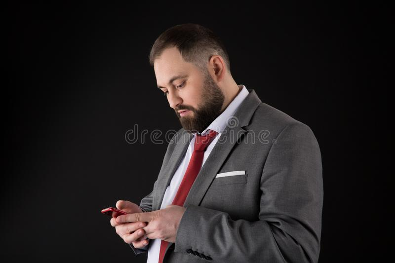 Businessman well groomed man hold smartphone. Man formal suit use smartphone social networks. Guy surfing internet smartphone stock photography