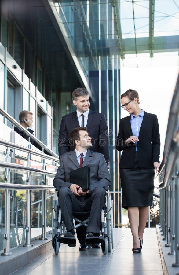 Businessman on wheelchair and his co-workers. Young businessman on wheelchair and his co-workers, vertical royalty free stock images
