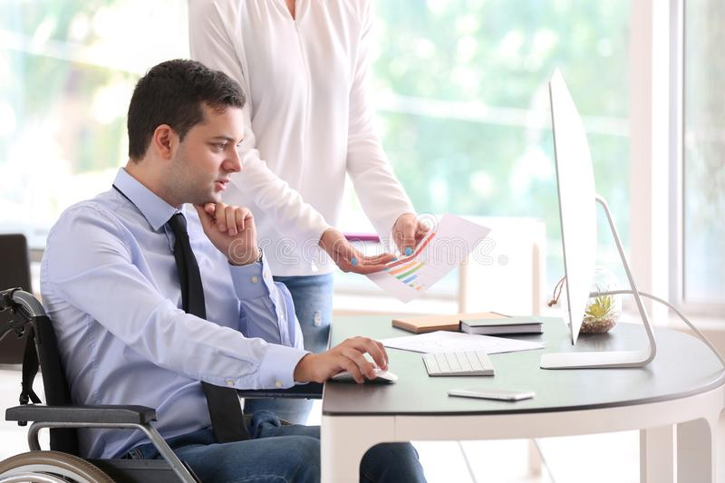 Businessman in wheelchair working with colleague in office stock images