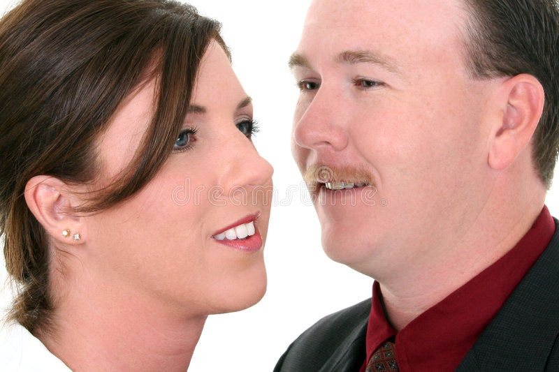 Businessman Whispering In Woman's Ear stock images