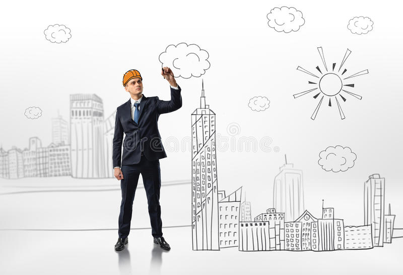 Businessman on white background drawing a cloud when several houses, a skyscraper, a sun and several clouds finished. Business and art. Inner talents royalty free stock photos