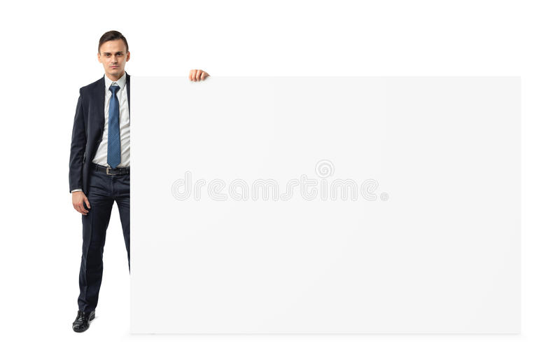 Businessman on white background holding a shoulder-height blank display board. royalty free stock images