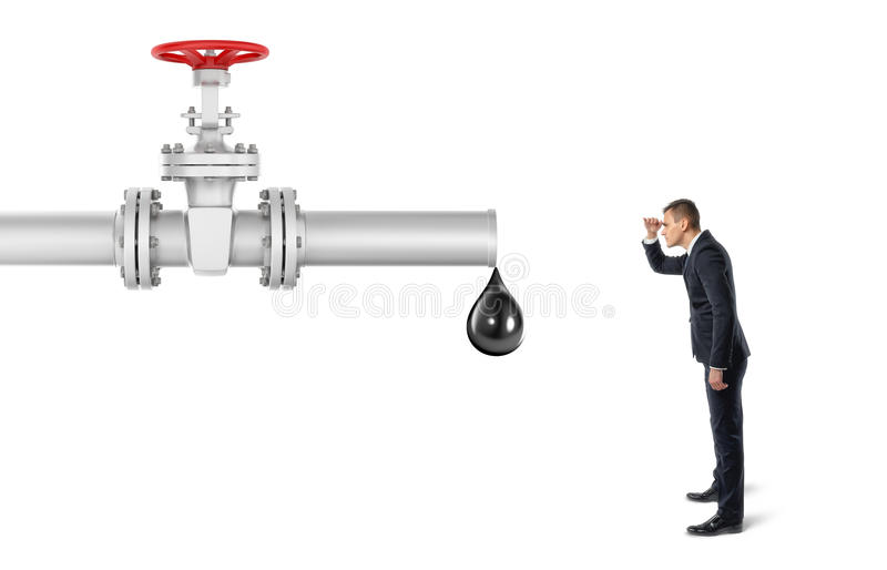 Businessman on white background looking at pipe with red valve that`s leaking one big oil drop royalty free stock photos