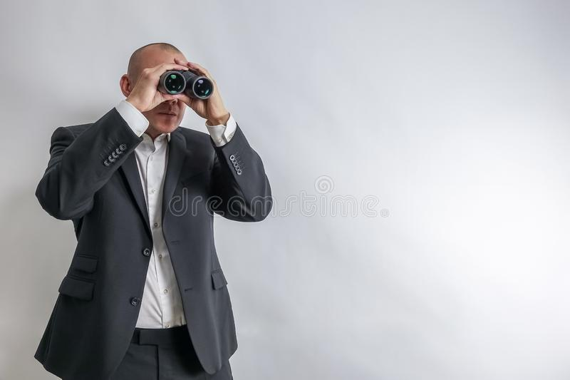 Businessman in white shirt and black suit scouts in binoculars. royalty free stock image