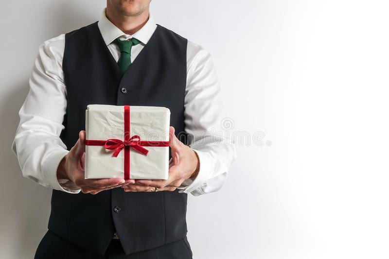 Businessman in suit vest holding a Christmas gift / present. stock photo