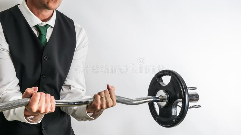 Businessman in suit vest performing biceps curl with EZ curl bar. stock images