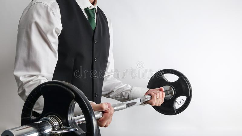 Businessman in suit vest performing biceps curl with EZ curl bar. Businessman in white shirt and black suit vest performing biceps curl with EZ curl bar stock photo