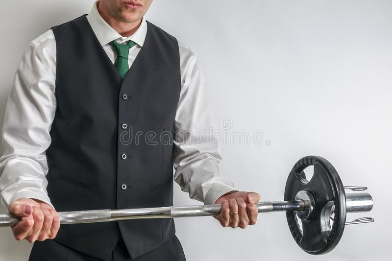 Businessman in suit vest performing biceps curl with EZ curl bar. Businessman in white shirt and black suit vest performing biceps curl with EZ curl bar royalty free stock images