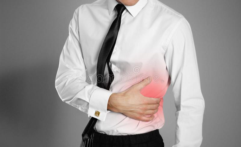 Businessman in a white shirt and tie holding his side. Pain in t stock images