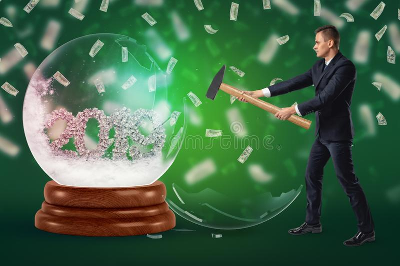 A businessman who has just crashed a crystal ball with the date `2019` inside formed with dollar bills with money stock images