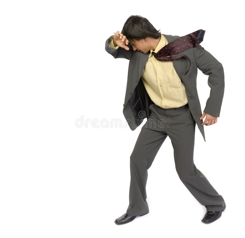 Businessman in the wind. Man's standing on strong wind. He's protecting his face by hand. Isolated on white in studio stock image