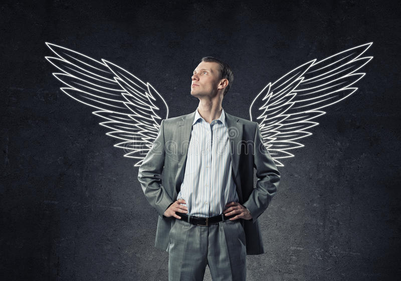 Businessman with wings. Young businessman with chalk drawn wings behind his back stock photography