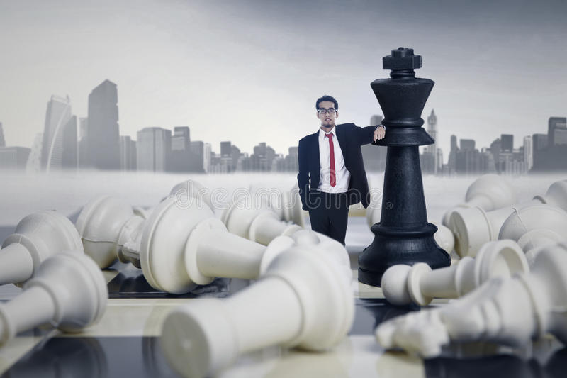 Businessman Winning Chess Game. On cityscape background stock images