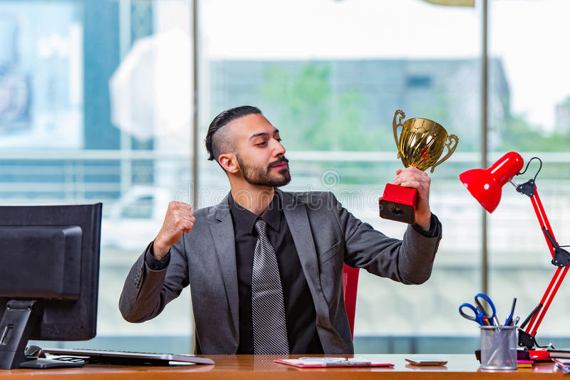 The businessman winning cup trophy in the office royalty free stock photo
