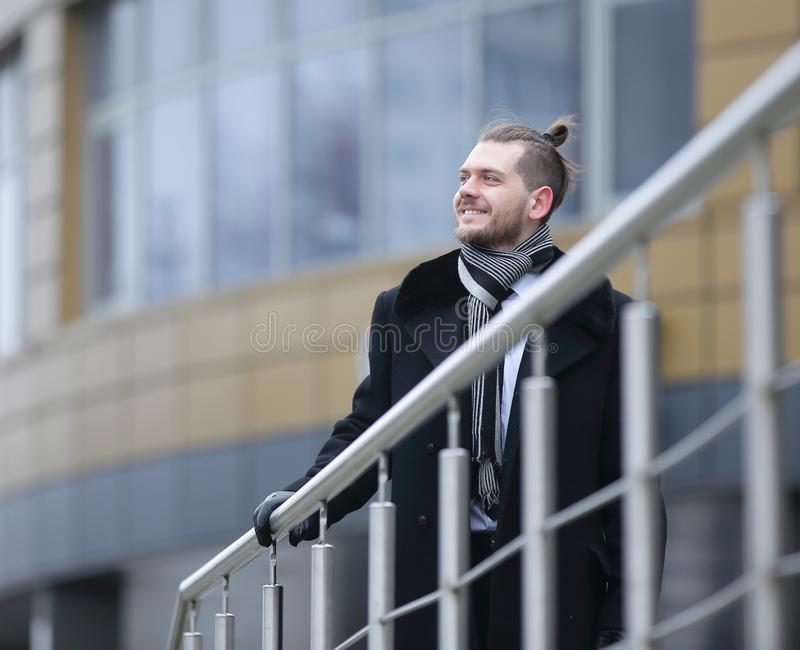 Businessman in winter coats ,standing near the office stock image