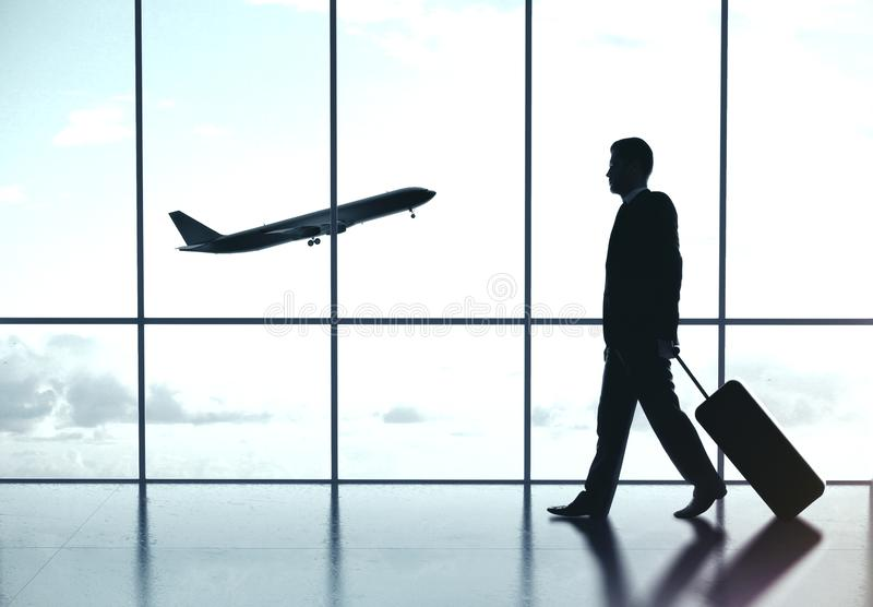 Businessman in airport. Businessman wolking in airport and airplane flying in sky. Travel and transportation concept stock photos