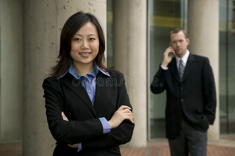 Businessman and Woman. Posing outside of an office building royalty free stock photos