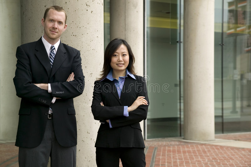 Businessman and Woman. Posing outside of an office building stock photos