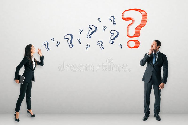 Communication and doubt concept. Businessman and woman asking each other questions on concrete wall background. Communication and doubt concept stock photo