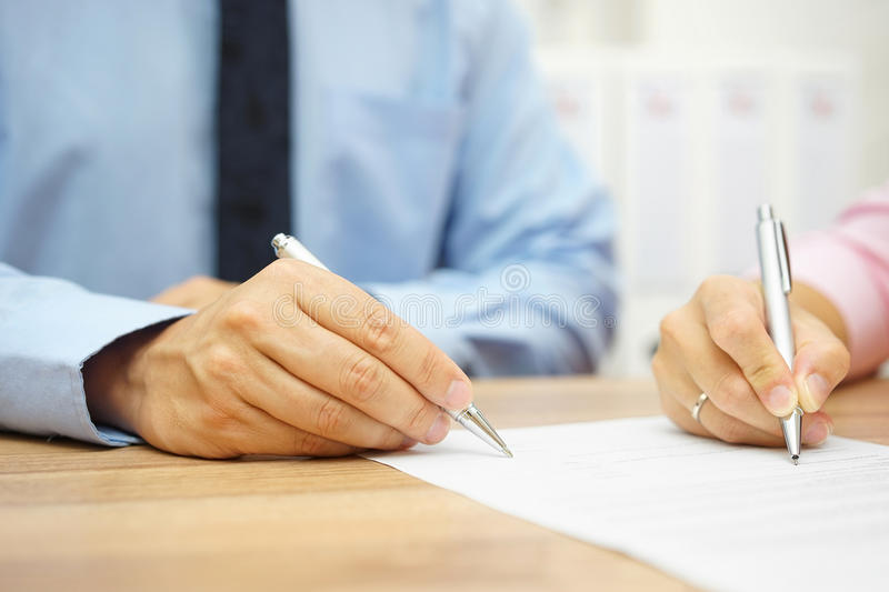 Businessman and woman hand signing agreement in office. A Businessman and woman hand signing agreement in office stock image