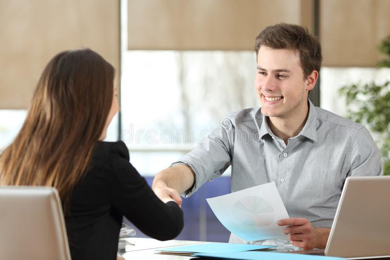 Businessman and woman handshaking at office stock photo