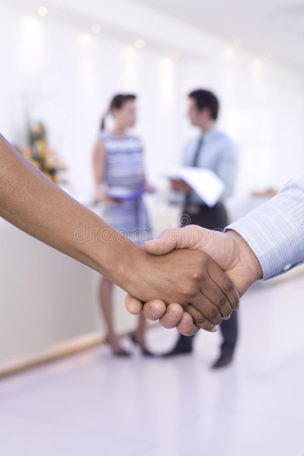 Businessman and woman shaking hands, colleagues in background, close-up of hands royalty free stock photography