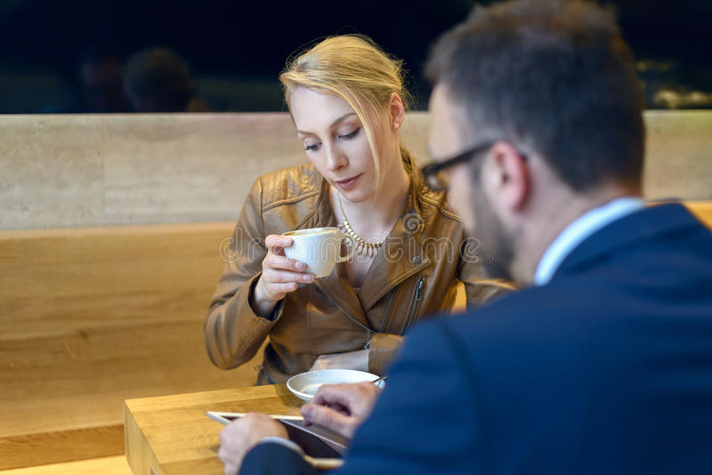 Businessman and woman sitting down to coffee. Businessman and women sitting down for coffee together in a cafeteria with the men showing something on his tablet stock photo