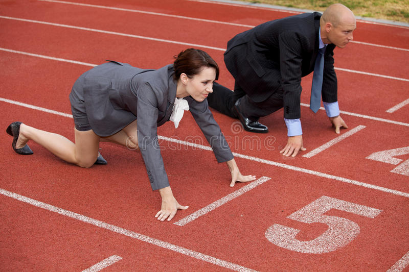 Download Businessman And Woman On Start Line Of Running Track Stock Photo