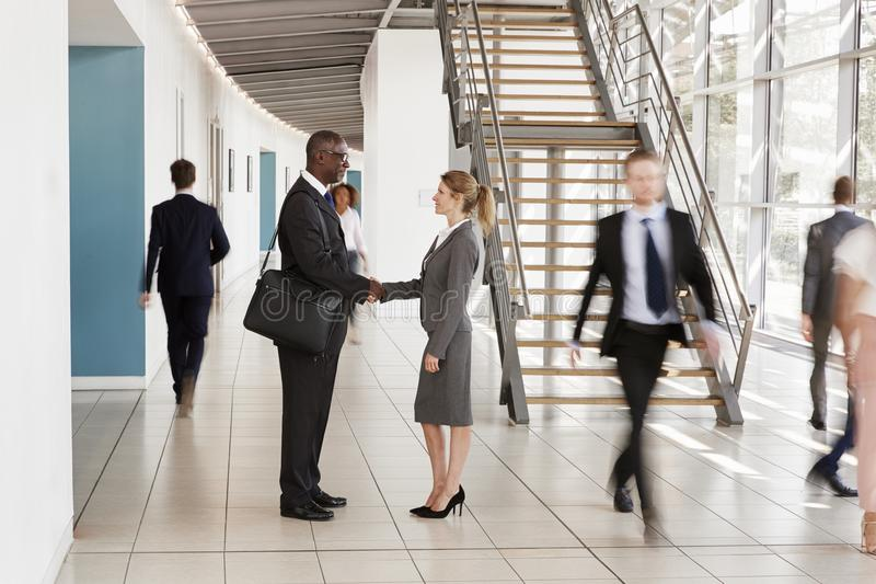Businessman and woman shaking hands in a busy modern lobby royalty free stock image