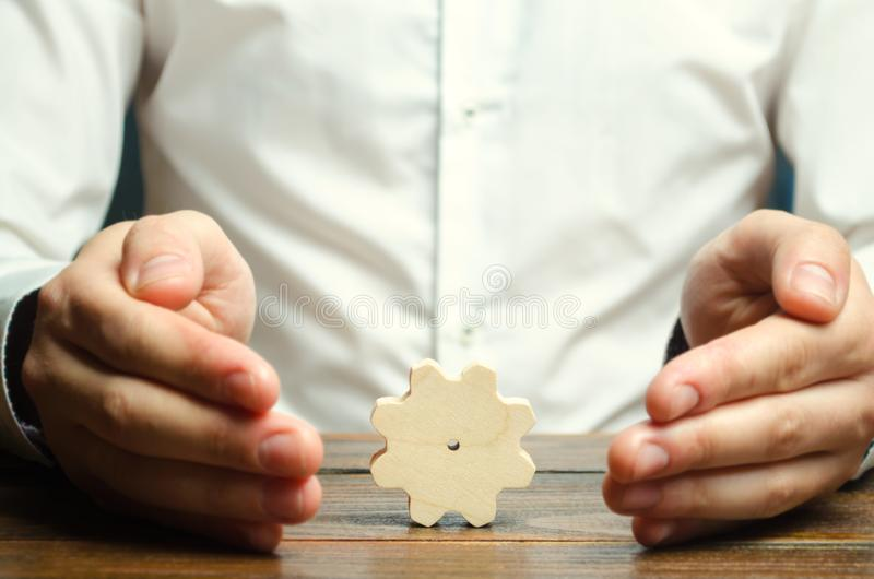 Businessman and wooden gear. Establishing business processes and communications. Development of business relations and cooperation. Efficiency increase and royalty free stock photos