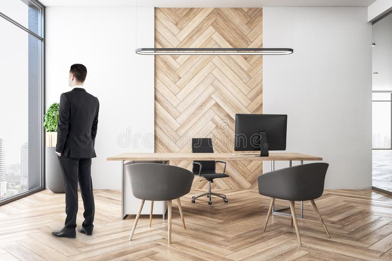 Businessman in wooden office. Side view of blurry businessman standing in wooden spacious office room interior with city view and daylight. Executive and royalty free stock images
