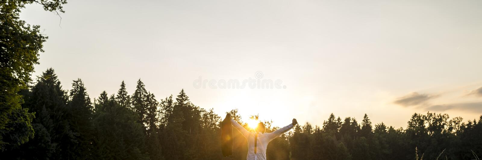 Businessman in a woodland with his arms outspread celebrating royalty free stock images