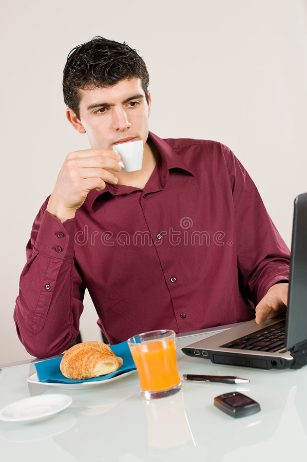 Businessman at work with breakfast. Young busy man studying and working on his laptop while having breakfast stock photography