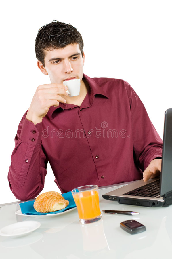 Businessman at work with breakfast. Young busy man studying and working on his laptop while having breakfast isolated on white background stock photos