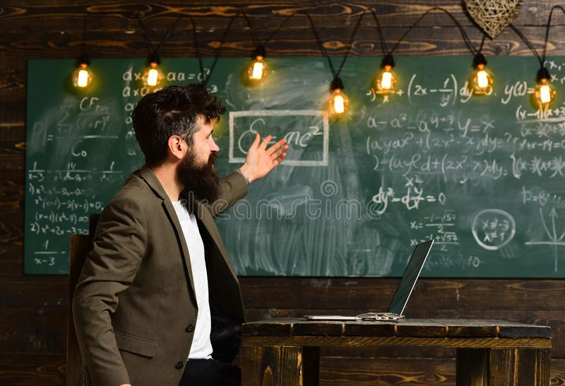 Businessman work on laptop in classroom. Businessman in suit with notebook point at chalkboard, new technology concept.  stock photo
