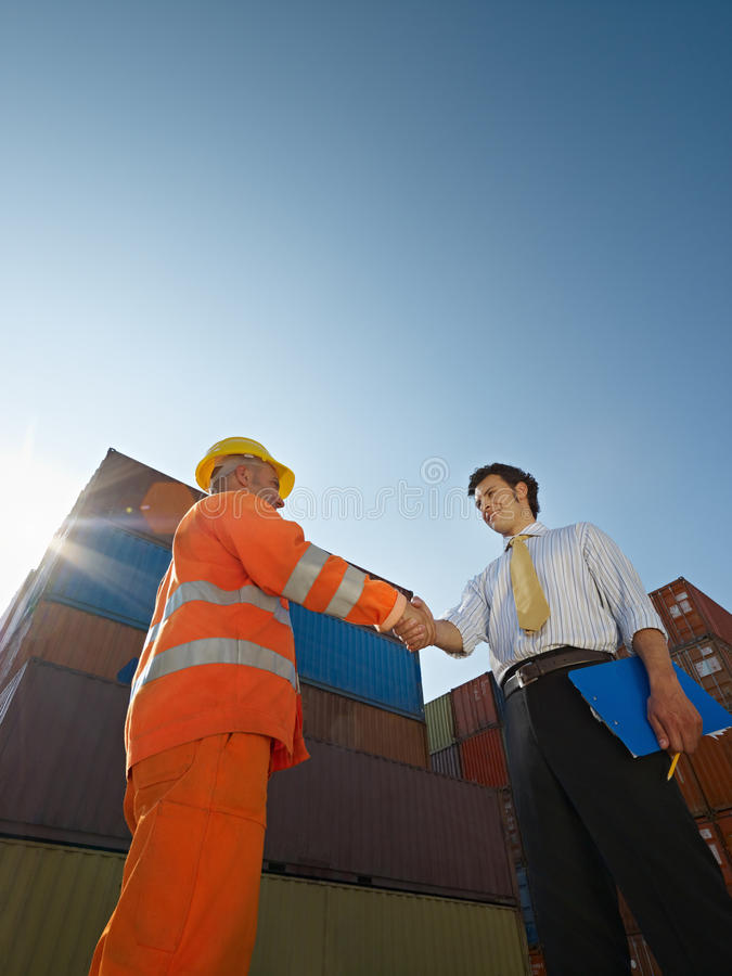 Businessman and worker with cargo containers stock photo