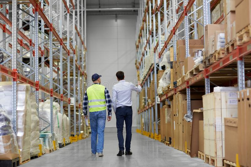 Businessman and worker walking along warehouse stock photo