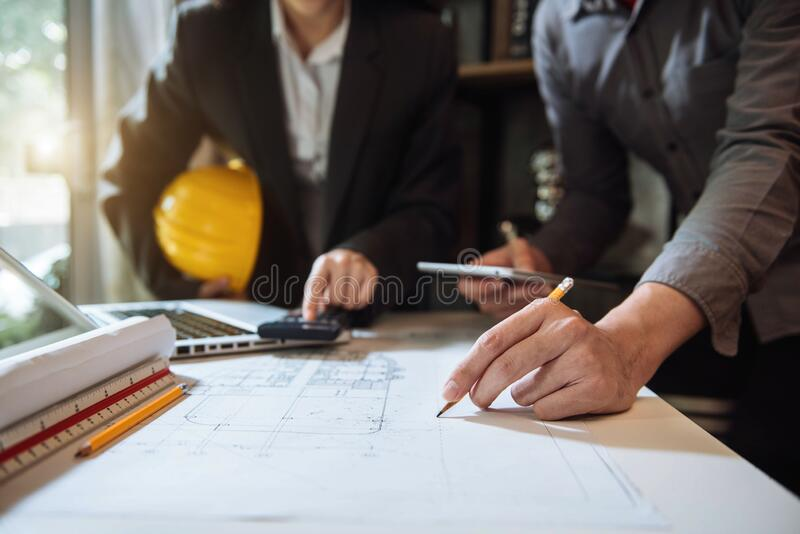Businessman working as a team discussing data working and tablet, laptop with on on architectural project. stock images