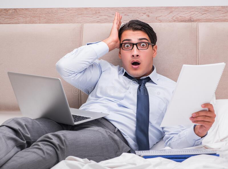 Businessman working in the bed at home royalty free stock photo